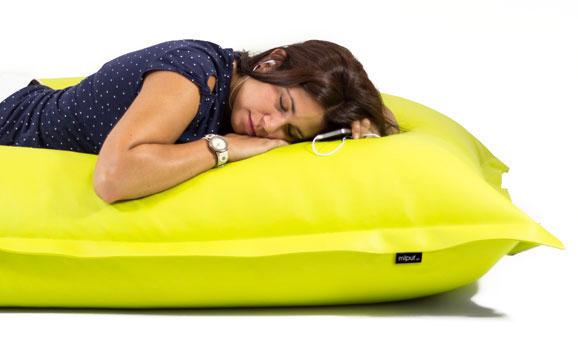 Chica joven descansando placenteramente en un puf